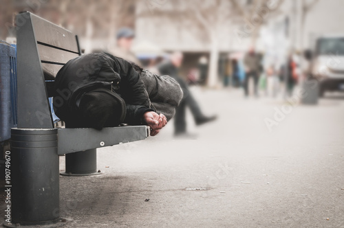 Fotomural Poor homeless man or refugee sleeping on the wooden bench on the urban street in