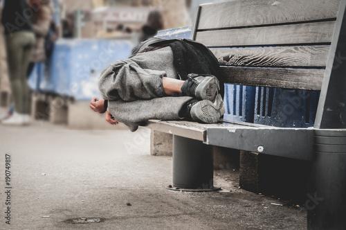 Fototapeta Poor homeless man or refugee sleeping on the wooden bench on the urban street in