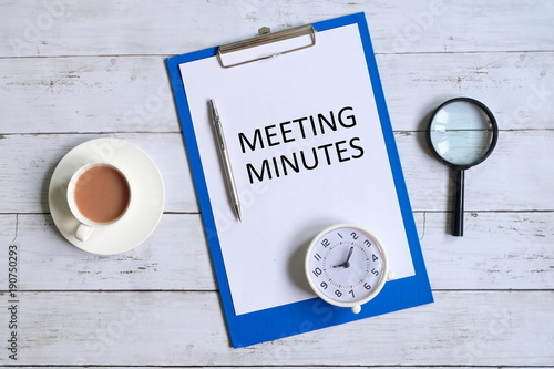 Fotografía  Top view of clipboard with paper written 'MINUTES MEETING' with magnifying glass,pen,table clock and a cup of coffee on white wooden background