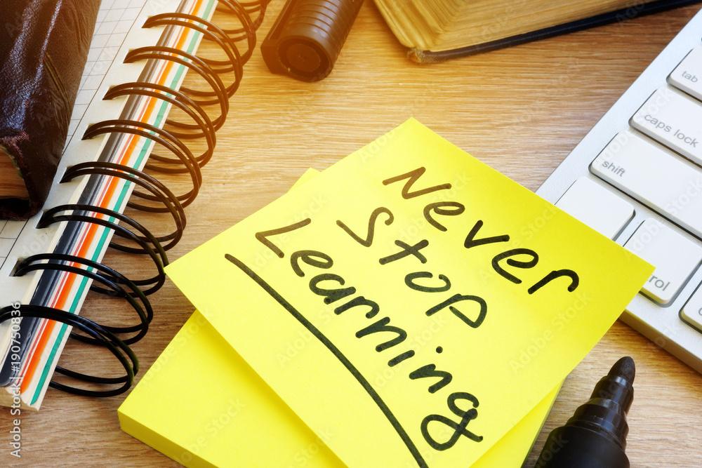 Fototapeta Never stop learning written on a memo stick. Lifelong learning concept.