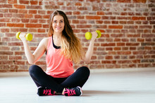 Blonde Fitness Woman Sitting With Yellow Dumbbells On The White Floor Befor Brick Wall.