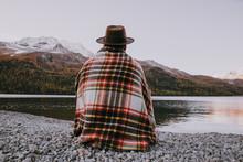 Lonely Man Enjoying Sunrise On A Lake Beach With Mountains Background