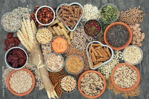 Assortiment Healthy high fibre dietary food concept with whole wheat pasta, legumes, nuts, seeds, cereals, grains and wheat sheaths. High in omega 3, antioxidants, vitamins. On marble background top view.
