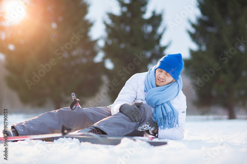 Poster Wintersporten Young sportsman rubbing his hit knee after crash in snow during ski training in park