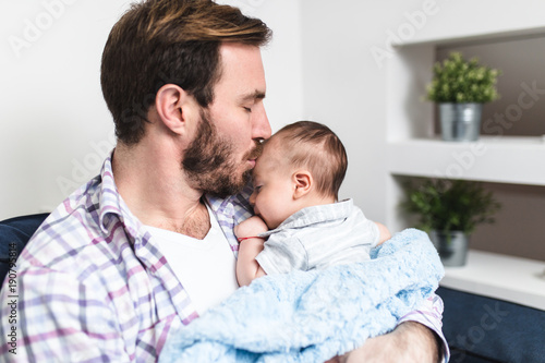 Handsome father holding his cute little baby boy. Tableau sur Toile
