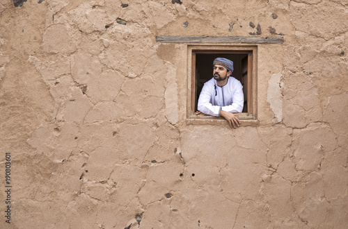 Photographie  arab man in traditional omani outfit in an old castle, looking out of a window