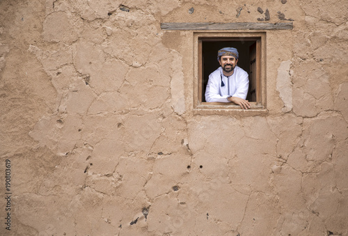 arab man in traditional omani outfit in an old castle, looking out of a window Tableau sur Toile
