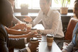 canvas print picture - Multi ethnic group of happy friends drinking coffee in paper cups together in cozy cafe, diverse multiracial african and caucasian young people talking sharing table having fun at coffeehouse meeting