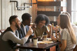 canvas print picture - Multiracial happy young people eating pizza in pizzeria, black and white cheerful mates laughing enjoying meal having fun sitting together at restaurant table, diverse friends share lunch at meeting