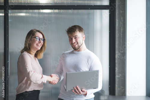 A Woman And Man Standing In The Background Of The Office Desk With A