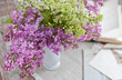 still life with a bouquet of lilac in a vase, book, postcards