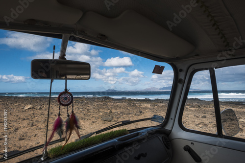 Fotografie, Obraz  interior of a minivan with dreamcathcer and ocean outside
