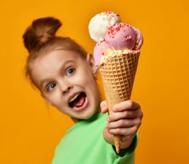 Fototapeta Do herbaciarni Pretty baby girl kid hold in hand banana and strawberry ice cream in waffles cone