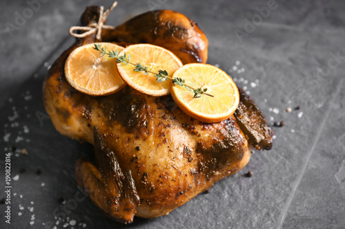 Fototapeta Delicious whole roasted chicken with orange served on slate plate obraz