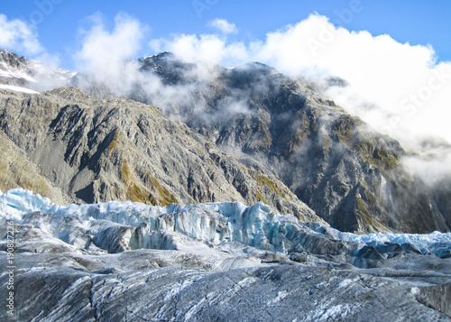 Valokuva  The Fox Glacier, covered in a fine layer of debris, as seen on a sunny day