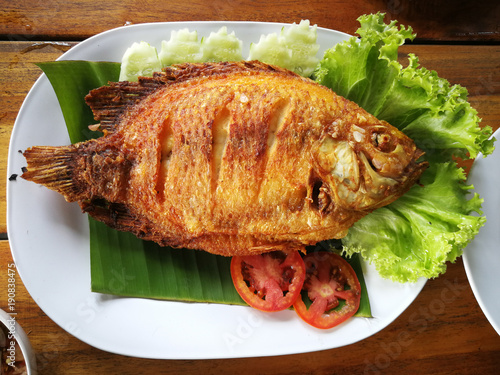 fried fish with vegetable on white dish top view, Delicious Asian fish fry served on a wooden table Canvas Print