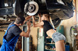 Mechanic shows the girl a brake disc on a hydraulic lift in a car repair shop. A guy in uniform, a girl in short shorts and T-shirt