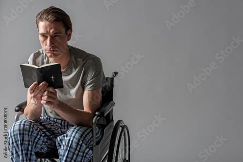 Valokuva  Portrait of frustrated invalid sitting in wheelchair and holding holy book