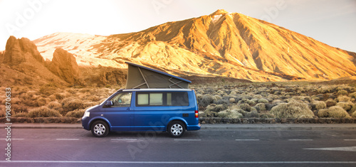 Photographie Small travel vehicle camping van or big car with folding rooftop with bed is parked under huge mountain formation