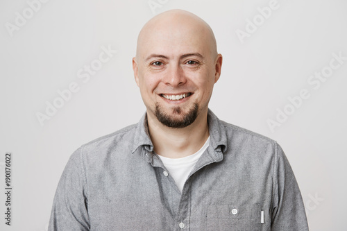 Carta da parati Close-up portrait of happy bald european with beard expressing confidence and reassurance, standing over gray background