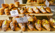 Various flavours of croissant or as in Italy their called brioche on display in a bakery in Milan, Italy with a price and sign - Albicocca means jam in Italian
