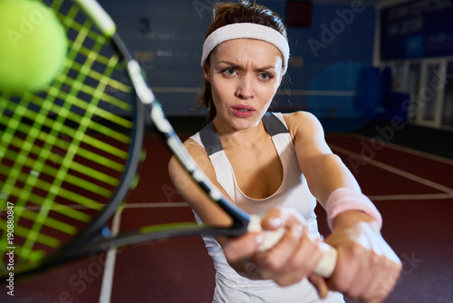Portrait Of Forceful Woman Playing Tennis In Indoor Court Frowning