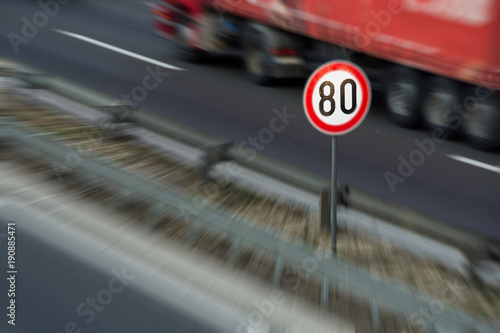 Fotografía  Defocused image of traffic sign showing speed limit on a highway with truck driv
