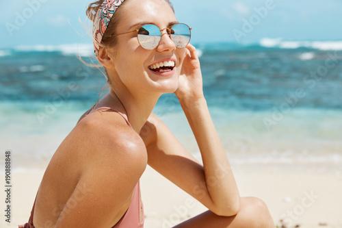 Valokuvatapetti Attractive female model wears headband and sunglasses, has perfect slim body, sm