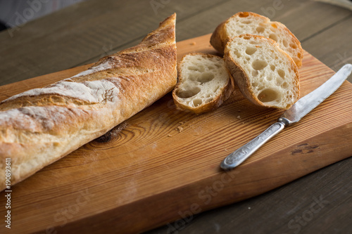 Fototapeta A baguette on a wooden background. obraz