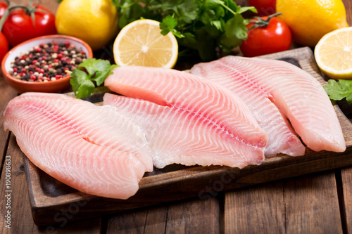 Fotografija fresh fish fillet with ingredients for cooking