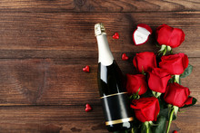 Champagne Bottle With Glasses, Silver Ring And Bouquet Of Red Roses On Wooden Table