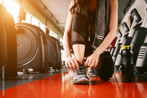 Deurstickers Fitness Sport woman tying sneakers rope. Sport center and Fitness gym concept. Healthy and Body build up theme. Sport wear and Fashion theme