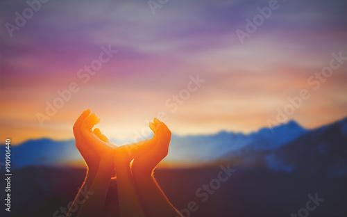 Human hands praying together at dawn Wallpaper Mural