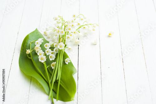 Staande foto Lelietje van dalen Lily of the valley on white wooden