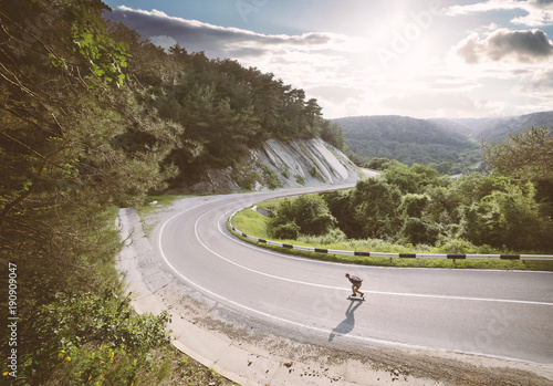 Young man go downhill on a longboard. Wallpaper Mural