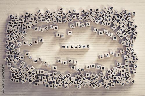 Obraz na plátně welcome - buchstaben-würfel mit begrüßung in vielen sprachen