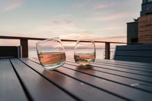 Two Tilted Tumbler Whiskey Glasses On Seaside Deck Table At Sunset