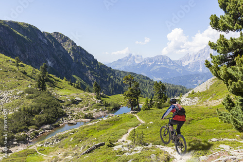 Obraz na płótnie Mountainbiker downhill on Reiteralm with mountain Dachstein in Styria Austria