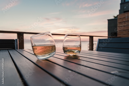 Two tilted tumbler whiskey glasses on seaside deck table at sunset Canvas Print