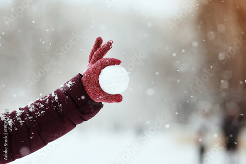 Fototapeta Close up of woman holding the snowball in hands, winter concept with copy space