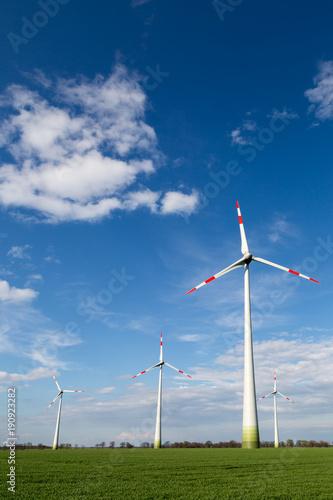 Zdjęcie XXL duże wiatraki stoją na polu i produkują zieloną energię elektryczną
