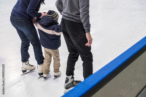 Fototapeta Happy family indoor ice skating at rink. Winter