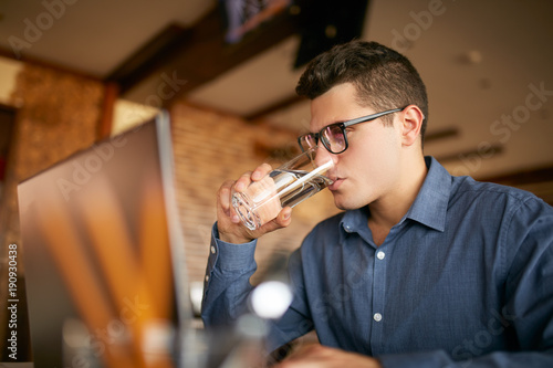 Handsome caucasian man with glass of water in hand works with laptop Canvas Print