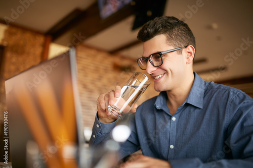 Stampa su Tela Smiling caucasian man with glass of water in hand works with laptop