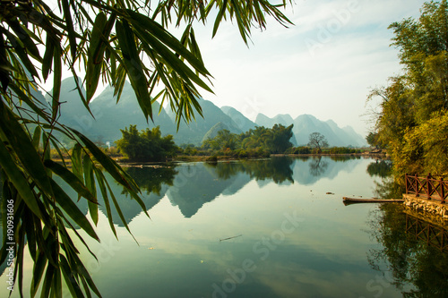 Foto auf AluDibond Reflexion Beautiful landscape of karst mountains reflected in water, Yulong river in Yangshuo South China.
