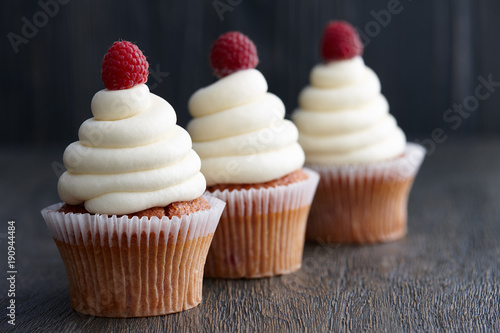Beautiful cupcakes with fresh raspberries on dark wooden background Canvas Print