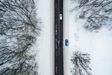 Trzy pokryte śniegiem samochody jeżdżą wzdłuż drogi. Widok z lotu ptaka. Zdjęcie z drona
