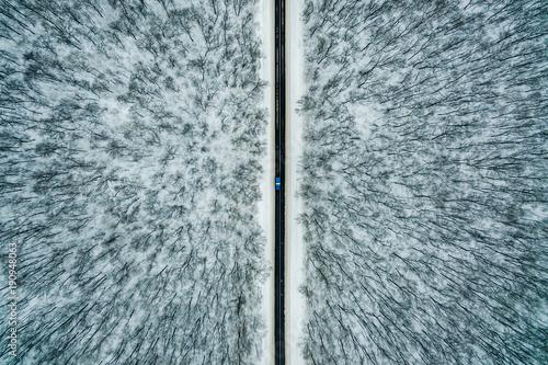 niebieski-samochod-jedzie-wzdluz-drogi-przez-zimowy-las-droga-widziana-z-powietrza-krajobraz-z-lotu-ptaka-fotografia-dronowa