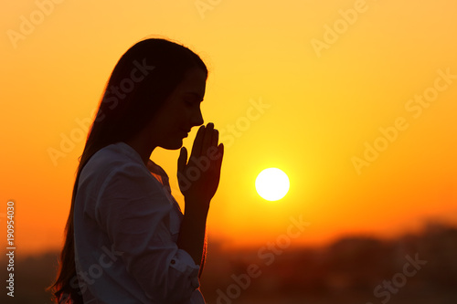 Backlight of a woman praying at sunset Canvas-taulu