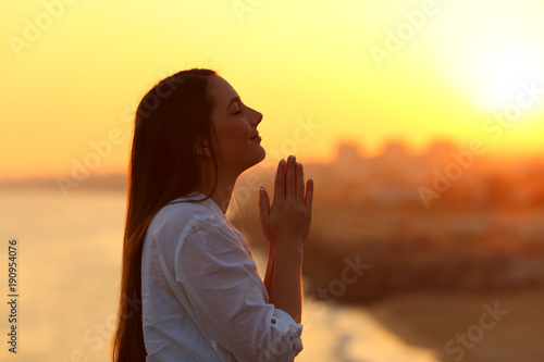 Fotografie, Obraz  Profile of a woman praying at sunset